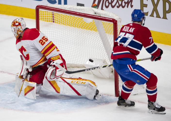 Montreal Canadiens' Brett Kulak (77) scores on Calgary Flames goaltender Jacob Markstrom (25) during the second period of an NHL hockey game Wednesday, April 14, 2021 in Montreal. (Ryan Remiorz/Canadian Press via AP)