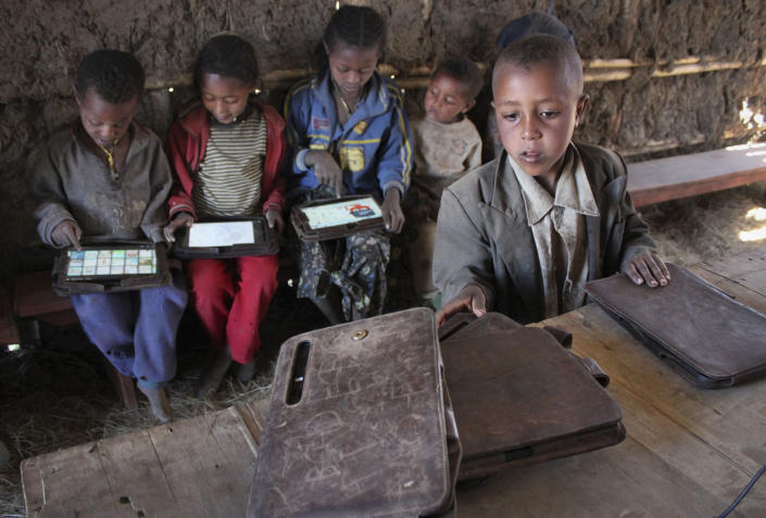 In this photo taken Tuesday, Nov. 27, 2012, a boy looks for his tablet computer as others play with theirs which were given by the One Laptop Per Child project in the village of Wenchi, Ethiopia. The project gave tablets to the children in the poor, illiterate village to see how much the children could teach themselves and now many kids can recite the English alphabet and spell words in English. (AP Photo/Jason Straziuso)