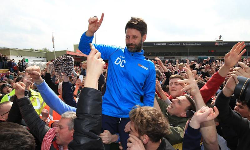 Lincoln's manager, Danny Cowley, is lifted by the jubilant supporters.