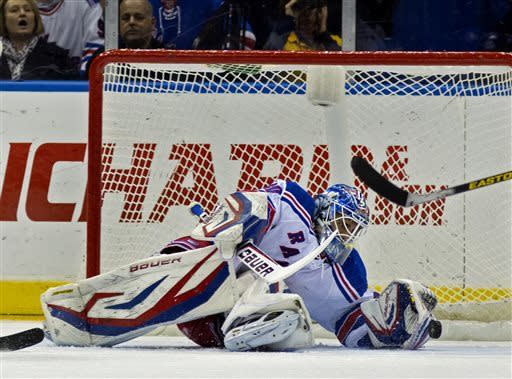 New York Rangers goalie Henrik Lundqvist stops the puck from entering the net against the New York Islanders in the first period of an NHL hockey game in Uniondale, N.Y., Saturday, April 13, 2013. (AP Photo/Craig Ruttle)