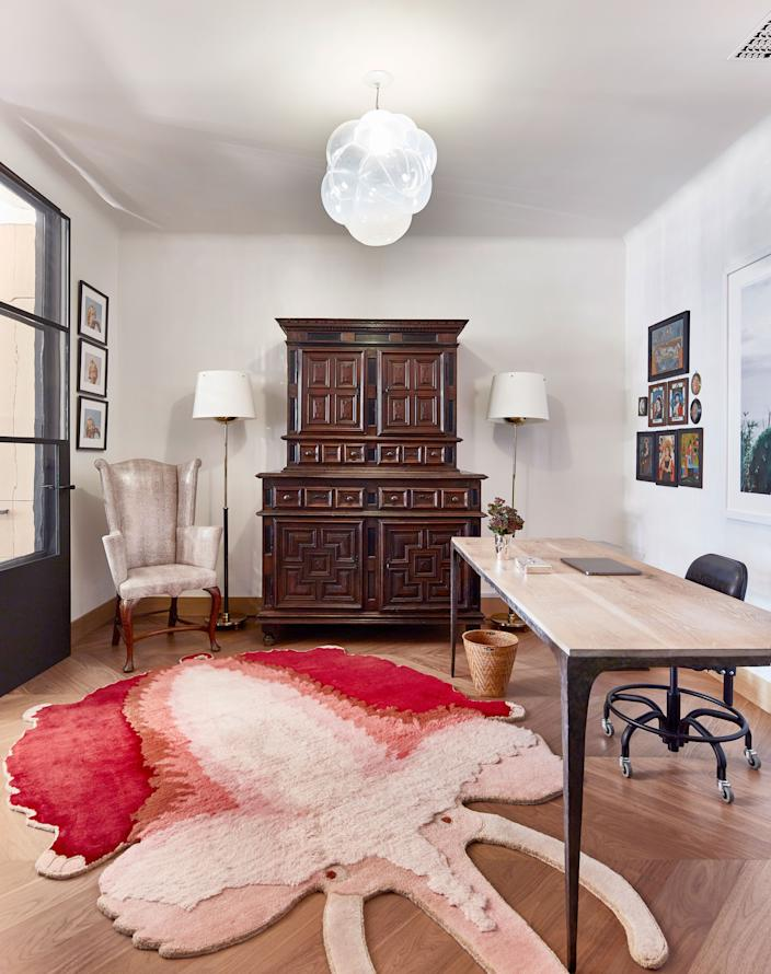 "<div class=""caption""> Even the home office packs a punch, thanks to the Haas Brothers' <em>La Brea Brad Pitt</em> mammoth rug. Antique pieces like the Portuguese cabinet have been blended with modern ones like the Oka desk. The hanging light from designer Jeff Zimmerman is made from handblown glass. </div>"