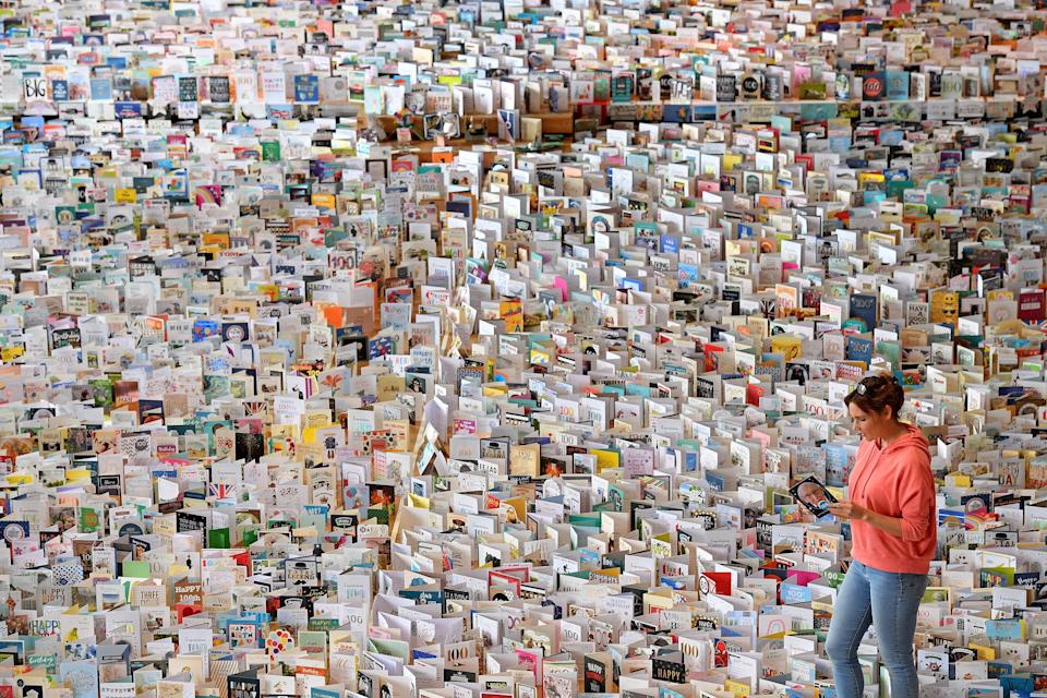 Mandy Alison poses with a selection of over 125,000 birthday cards sent to Captain Tom Moore, for his 100th birthday on April 30th, but displayed in the Great Hall of Bedford School, closed-down due to the COVID-19 pandemic, in Bedford, north of London, on April 28, 2020. - 99-year-old Moore captured the hearts of the UK after initially setting out to raise just £1,000 for Britain's National Health Service (NHS) following the novel coronavirus outbreak, by walking 100 laps of his 25-metre (82-foot) garden, but went on to brake the record for raising the most money in an individual charity walk -- more than £27 million ($33 million, 31 million euros). (Photo by JUSTIN TALLIS / AFP) (Photo by JUSTIN TALLIS/AFP via Getty Images)
