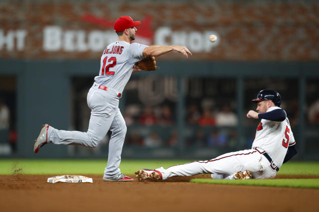 St. Louis Cardinals shortstop Paul DeJong (12) throws to first after the force out of Atlanta Braves Freddie Freeman (5) during the fifth inning of a baseball game Tuesday, Sept. 18, 2018, in Atlanta. Nick Markakis was safe at first. (AP Photo/Todd Kirkland)
