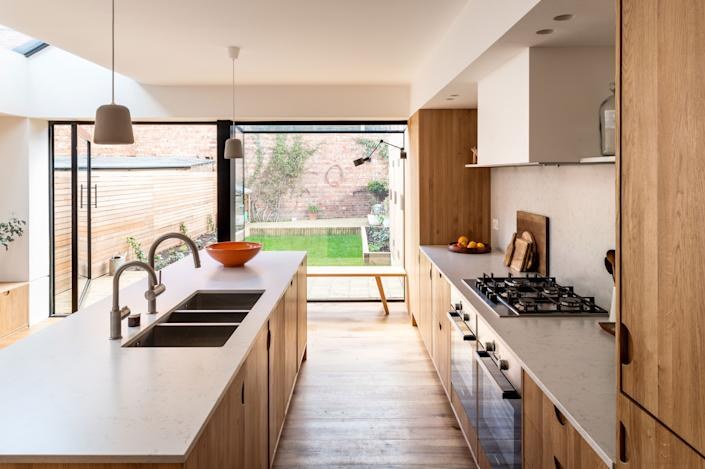 """<div class=""""caption""""> A single, massive pivot door opens the kitchen up to the backyard. </div> <cite class=""""credit"""">FRENCH+TYE</cite>"""