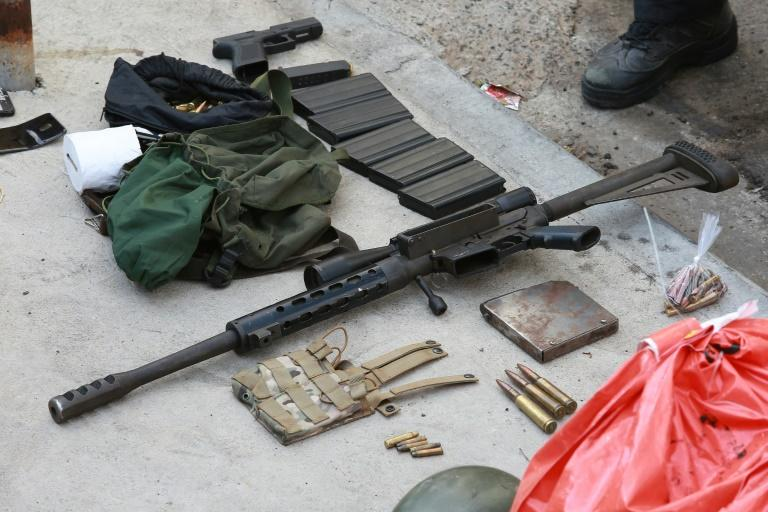 A gun, money bag and other items seized from criminals who raided the cargo terminal of the Viracopos International Airport, in Campinas, Sao Paulo state, Brazil, on October 17, 2019 (AFP Photo/LEANDRO FERREIRA)