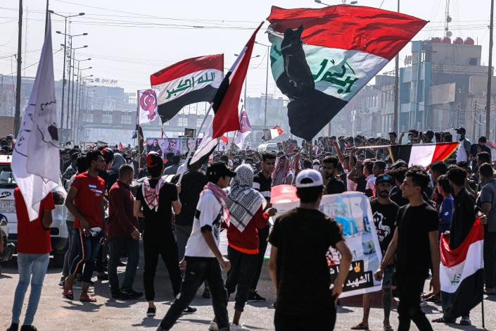 Protesters wave national flags during anti-government protests in Basra, Iraq, Sunday, Oct. 25, 2020. Thousands of Iraqi protesters have taken to the streets to mark one year since mass anti-government demonstrations swept Baghdad and Iraq's south. Protesters marched Sunday in the capital and several southern cities to renew demands to bring an end to corruption perpetuated by Iraq's politicians. (AP Photo/Nabil al-Jurani)
