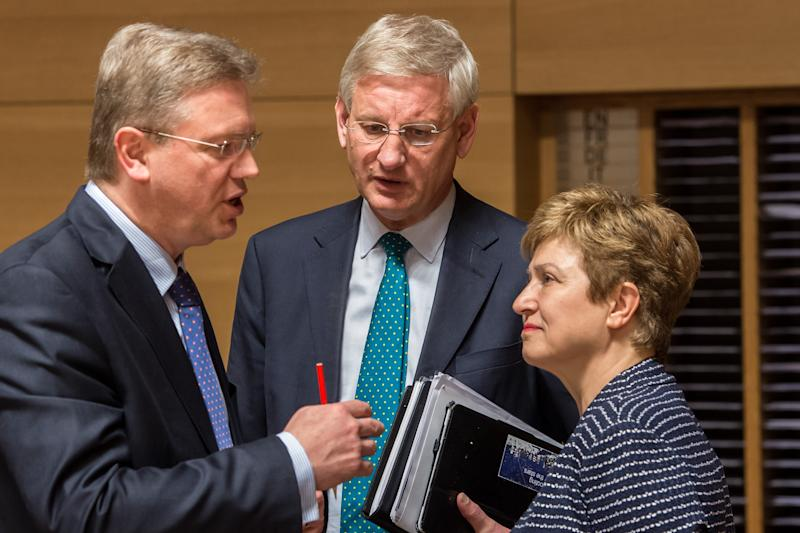 CORRECTING FOR MAN AT LEFT TO BE UNIDENTIFIED - An unidentified delegate, left, talks with Sweden's Foreign Minister Carl Bildt, center, and European Commissioner for International Cooperation, Humanitarian Aid and Crisis Response Kristalina Georgieva at the start of an EU foreign ministers meeting at the Kirchberg Conference Center in Luxembourg, Monday, April 22, 2013. (AP Photo/Geert Vanden Wijngaert)