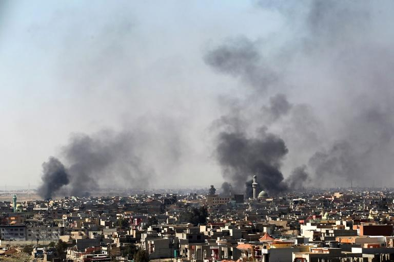 Smoke billows from the Al-Amil neighborhood of west Mosul as Iraqi forces pound Islamic State group positions on March 10, 2017, in fighting that has prompted more and more civilians to flee