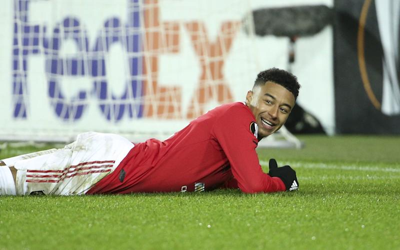 Jesse Lingard lies on the pitch smiling - GETTY IMAGES