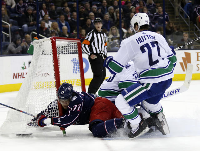 Columbus Blue Jackets forward Josh Anderson, left, collides with the goal in front of Vancouver Canucks goalie Jacob Markstrom, center, of Sweden, and defenseman Ben Hutton during the second period of an NHL hockey game in Columbus, Ohio, Tuesday, Dec. 11, 2018. (AP Photo/Paul Vernon)