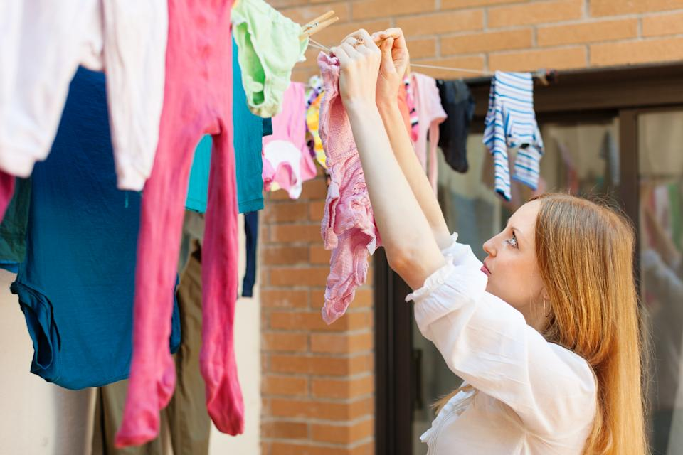long-haired girl drying clothes on clothes-line after laundry