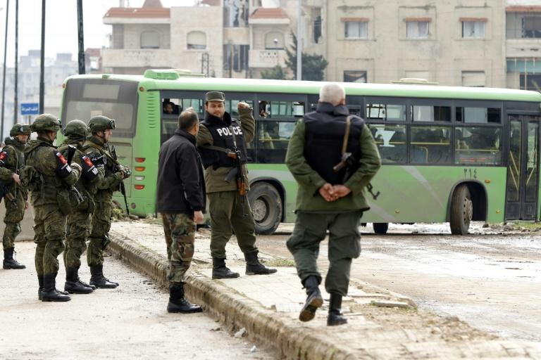 Russian military police stand guard as a bus drives past on Septmber 18, 2017 during the first phase of the evacuation of rebels from the last district they controlled in Syria's third city Homs. Up to 100 have been deployed to oversee the operation