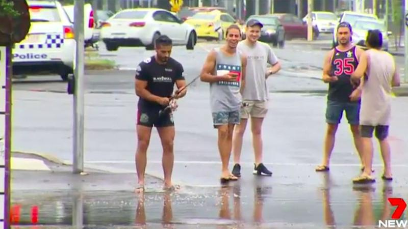 With his mates watching on and cars floating away, this man decided it was time to fish. Source: 7 News