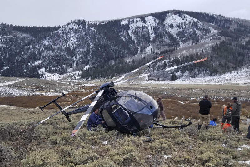 In this photo taken Monday, Feb. 12, 2018, and provided by the Wasatch County Sheriff's Office is a research helicopter that was brought down by a leaping elk in the mountains of eastern Utah. Wasatch County authorities say the elk jumped into the chopper's tail rotor as the craft flew low, trying to capture the animal with a net. The two people on board weren't seriously hurt, but wildlife officials say the elk died of its injuries. The state-contracted Australian crew had been trying to capture and sedate the elk so they could collar it and research its movements about 90 miles east of Salt Lake City. (Jared Rigby/Wasatch County Sheriff's Office via AP)