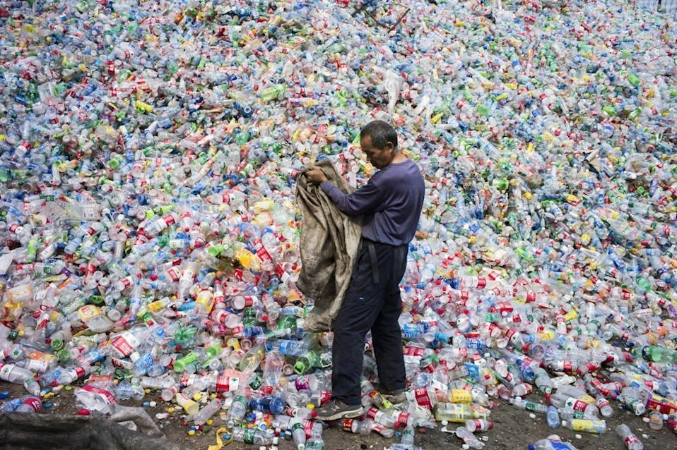 A labourer sorting out plastic bottles for recycling on the outskirts of Beijing. Photo: AFP