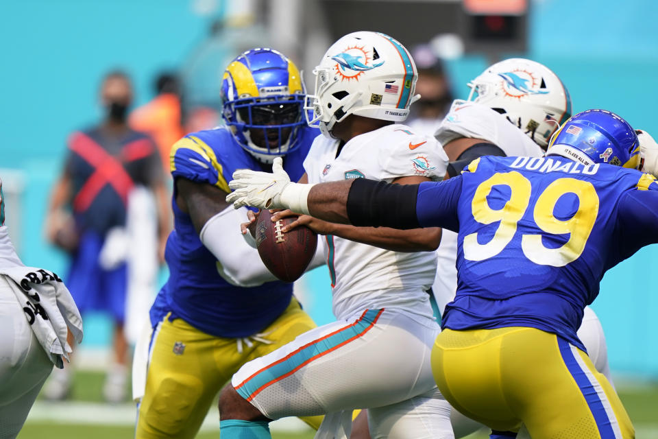 Los Angeles Rams defensive end Aaron Donald (99) goes after Miami Dolphins quarterback Tua Tagovailoa (1) during the first half of an NFL football game, Sunday, Nov. 1, 2020, in Miami Gardens, Fla. Tagovailoa fumbled the ball. (AP Photo/Wilfredo Lee)