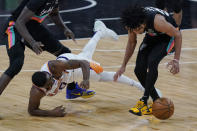 Phoenix Suns guard E'Twaun Moore (55) loses the ball to San Antonio Spurs guard Tre Jones, right, as he is tripped up during the second half of an NBA basketball game in San Antonio, Sunday, May 16, 2021. (AP Photo/Eric Gay)