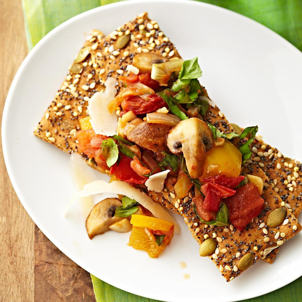 <p>In this quick, Italian-inspired snack or appetizer recipe, whole-grain flatbread crackers get topped with peppers, mushrooms, tomato and a sprinkling of shaved Parmesan cheese.</p>