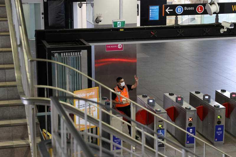 A masked worker gestures to a colleague at the Circular Quay train station in Sydney.