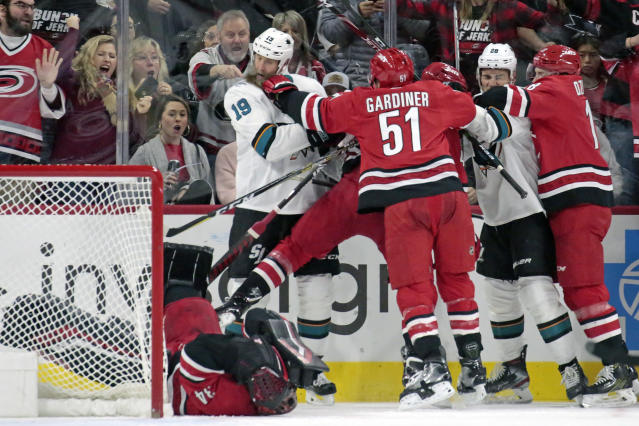 Carolina Hurricanes' Jake Gardiner (51) and Ryan Dzingel (18) tussle with San Jose Sharks' Joe Thornton (19) and Timo Meier (28) of Switzerland after Thornton knocked Carolina goaltender Petr Mrazek (34) of the Czech Republic to the ice during the second period of an NHL hockey game in Raleigh, N.C., Thursday, Dec. 5, 2019. Thornton and Mrazek were penalized on the play. (AP Photo/Chris Seward)