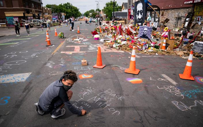 Anthony Land-Closson, 11, of Wheat Ridge, Colo., draws with chalk at the George Floyd memorial outside Cup Foods, Thursday, June 25, 2020, in Minneapolis - Leila Navidi/Star Tribune
