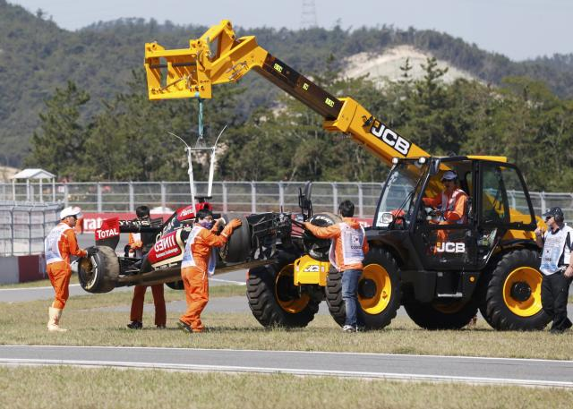 Workers remove the car of Lotus Formula One driver Kimi Raikkonen of Finland after it crashed during the first practice session of the Korean F1 Grand Prix at the Korea International Circuit in Yeongam October 4, 2013. REUTERS/Lee Jae-Won (SOUTH KOREA - Tags: SPORT MOTORSPORT F1)