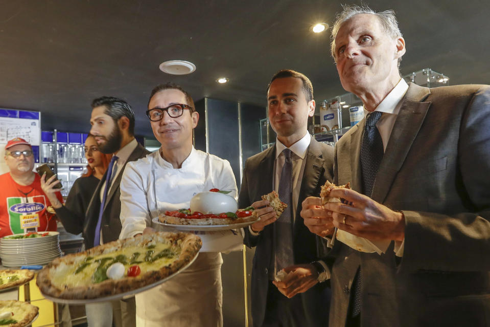 """Italian Foreign Minister Luigi Di Maio, center, eats a pizza with French Ambassador to Rome Christian Masset, right, as pizza maker Gino Sorbillo holds up pizzas in his restaurant, in Rome, Wednesday, March 4, 2020. According to reports, Di Maio invited the French ambassador for a pizza after French channel Canal plus broadcast a satirical video of a fake Italian pizza maker coughing on a pizza and calling it """"Corona Pizza"""". (AP Photo/Andrew Medichini)"""