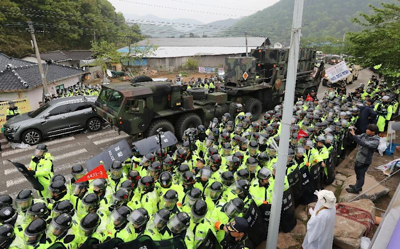 Protesters and police gather to watch as trailers carrying US THAAD missile defence equipment enter a deployment site in Seongju, South Korea (AFP Photo/YONHAP)