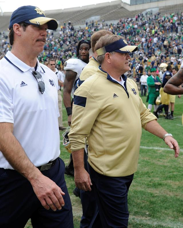 Notre Dame coach Brian Kelly, right, and defensive coordinator Brian VanGorder walk off the field after Notre Dame's spring NCAA college football game Saturday April 12, 2014 in South Bend, Ind. The Blue Gold game marks the end of spring football practice