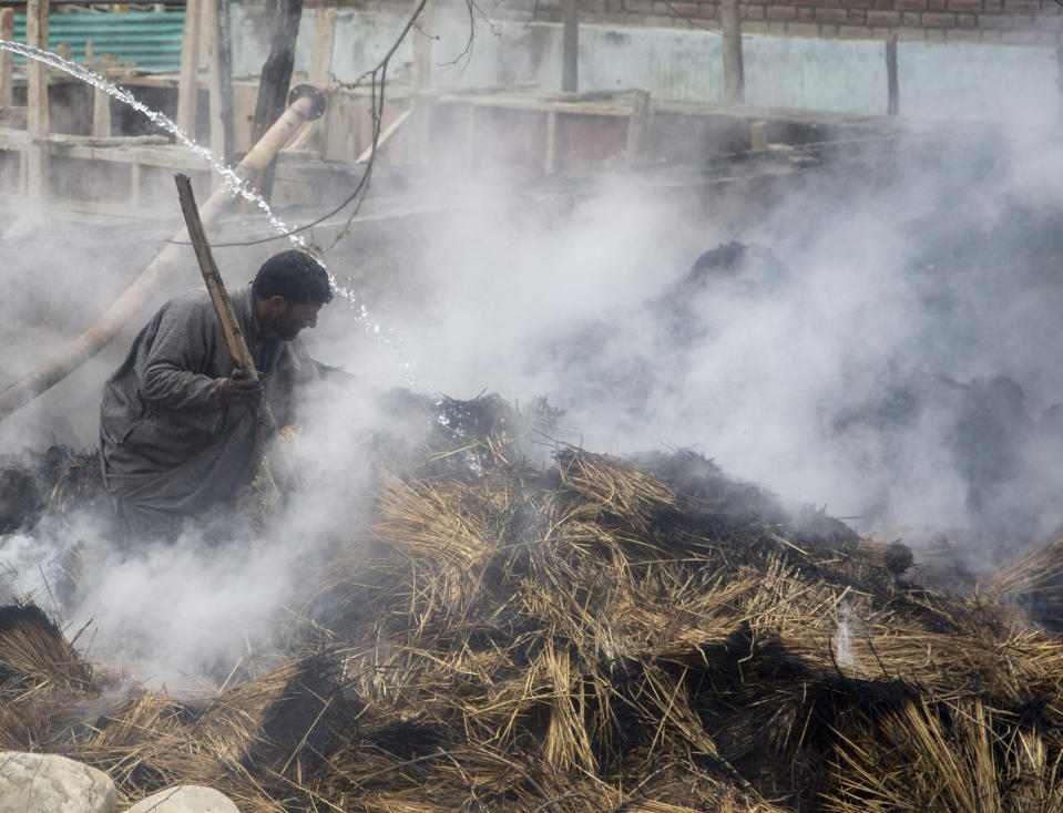 A Kashmiri man tries to douse the fire after fodder caught fire during a gun battle between government forces and suspected rebels in Bijbehara, some 28 miles (45 kilometers) south of Srinagar, Indian controlled Kashmir, Sunday, April 11, 2021. (AP Photo/Mukhtar Khan)