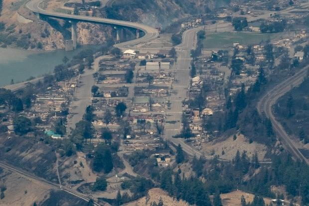 Structures destroyed by wildfire are seen in Lytton, B.C. The province said 'most homes' and structures in the village were destroyed after a fast-moving fire suddenly tore through the community, forcing more than 1,000 people to flee the area.  (Darryl Dyck/The Canadian Press - image credit)