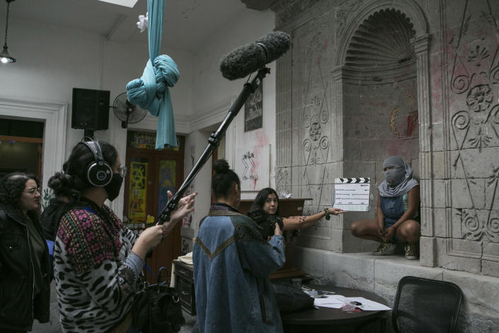 """A 10-year-old victim of sexual abuse, who keeps her face covered to hide her identity, poses for an all-female documentary crew from """"Las Rudas Film"""" inside the Mexican Human Rights Commission (CNDH) where she has been living with her mother, also a victim of sexual abuse when she was a child after women's rights activists occupied the building and turned it into a refuge almost three months prior in Mexico City, Tuesday, Nov. 17, 2020. The girl's mother Erika Martinez said she filed a complaint three years ago with the Prosecutor for Sexual Crimes after her daughter was abused when she was just 7 by her brother-in-law, but that he remains free. (AP Photo/Ginnette Riquelme)"""