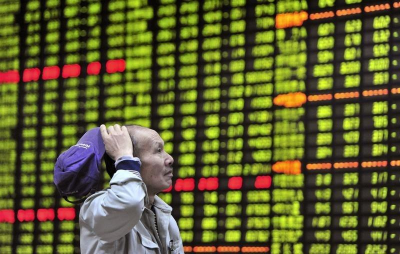 An investor looks at an electronic board showing stock information at a brokerage house in Jiujiang