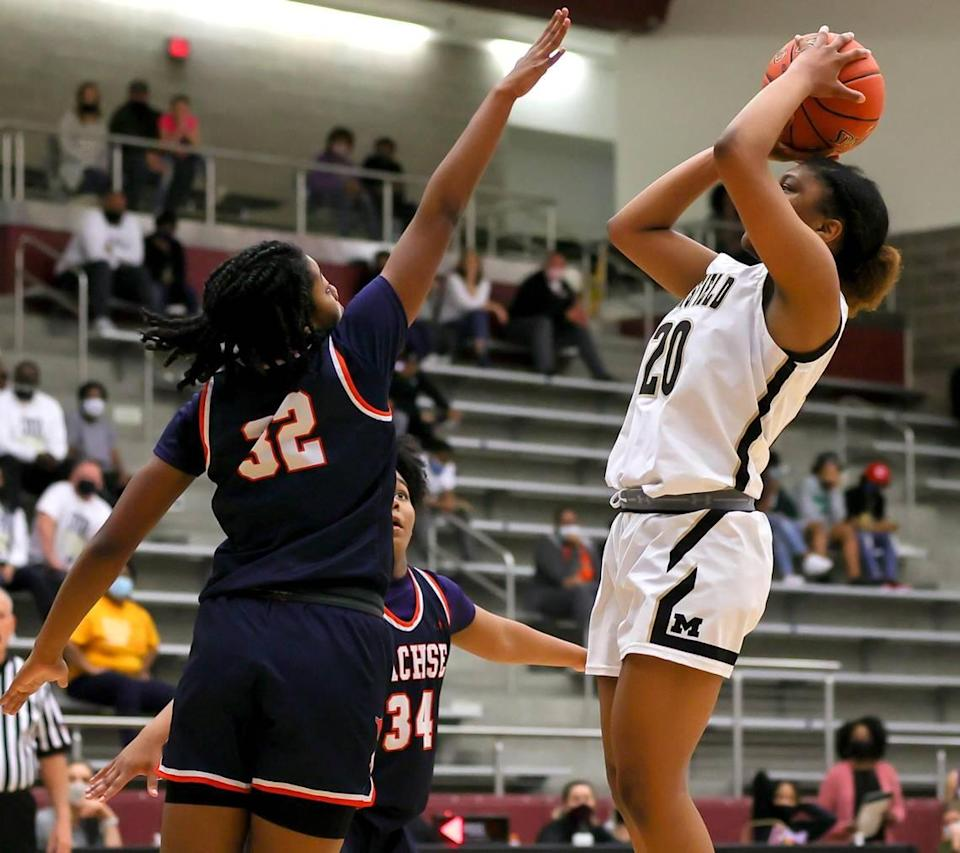 Mansfield guard Kendyl Howell (20) tries to get off a shot over Sachse guard Micah Cooper (32) during the second half of the 6A Region II Girls Basketball Area -Round 2 played February 23, 2021 at Lewisville High School. (Steve Nurenberg Special to the Star-Telegram)