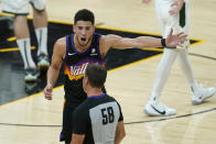 Phoenix Suns guard Devin Booker, top, gestures while talking with referee Josh Tiven (58) during the second half of Game 5 of basketball's NBA Finals between the Suns and the Milwaukee Bucks, Saturday, July 17, 2021, in Phoenix. (AP Photo/Ross D. Franklin)