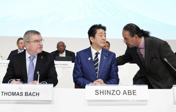 FILE - In this Nov. 28, 2018, file photo, Japanese Prime Minister Shinzo Abe, center, and IOC President Thomas Bach, left, listen to Sheikh Ahmad al Fahad al Sabah, president of the Association of National Olympic Committees (ANOC), during the opening of the ANOC general assembly in Tokyo. Japan wants to start using the traditional order for Japanese names in English in official documents, with family names first, a switch from the Westernized custom the country adopted more than a century ago. (AP Photo/Eugene Hoshiko, File)