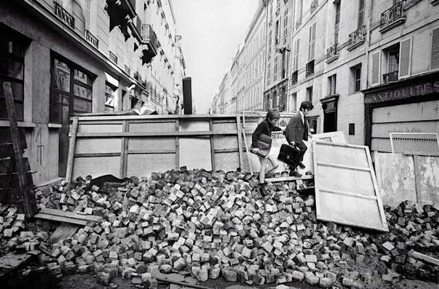 <p>Although universities were closed during the student riots, elementary schools remained open, and young children attended classes, climbing over paving stones at a barricade erected by students, Rue de l'Université, Paris, June 11, 1968. (Photo: Gökşin Sipahioğlu/SIPA) </p>