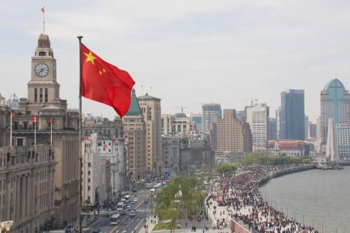 Chinese flag in foreground with The Bund in Shanghai in the background