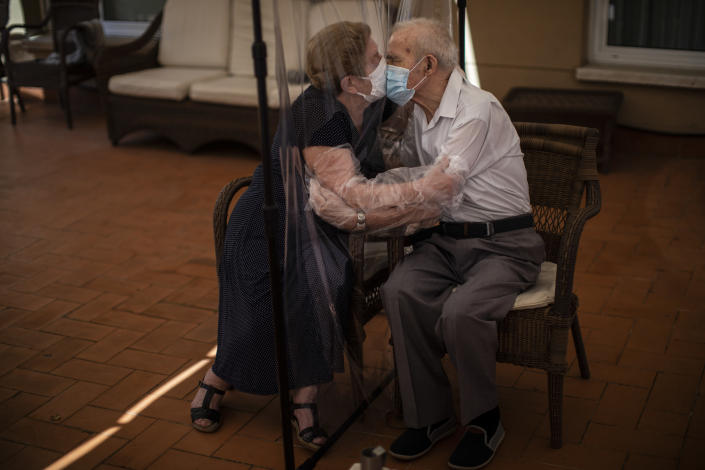 Agustina Cañamero, 81, hugs and kisses her husband Pascual Pérez, 84, through a plastic film screen to avoid contracting the coronavirus at a nursing home in Barcelona, Spain, June 22, 2020. Even when it comes wrapped in plastic, a hug can convey tenderness and relief, love and devotion. The fear that gripped Agustina Cañamero during the 102 days she and her 84-year-old husband spent physically separated during Spain's coronavirus outbreak dissolved the moment the couple embraced through a screen of plastic film. The image was part of a series by Associated Press photographer Emilio Morenatti that won the 2021 Pulitzer Prize for feature photography. (AP Photo/Emilio Morenatti)