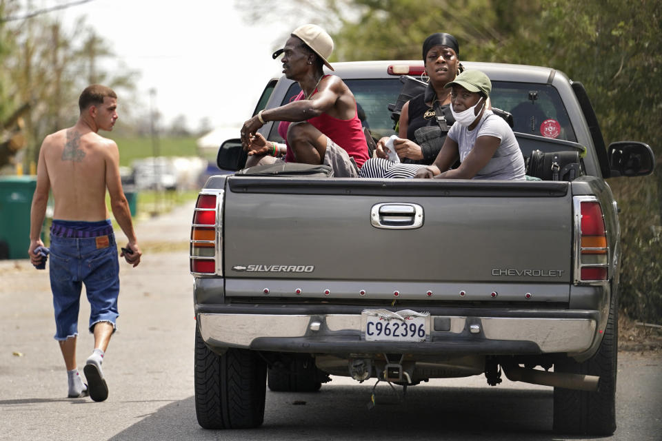 Linda Smoot, right, Rakisha Murray, center, and Bernie Murray who evacuated from Hurricane Laura in a pickup truck with eight others, react to the scenes of devastation as they return to see their homes for the first time, in Lake Charles, La., in the aftermath of the hurricane, Sunday, Aug. 30, 2020. (AP Photo/Gerald Herbert)