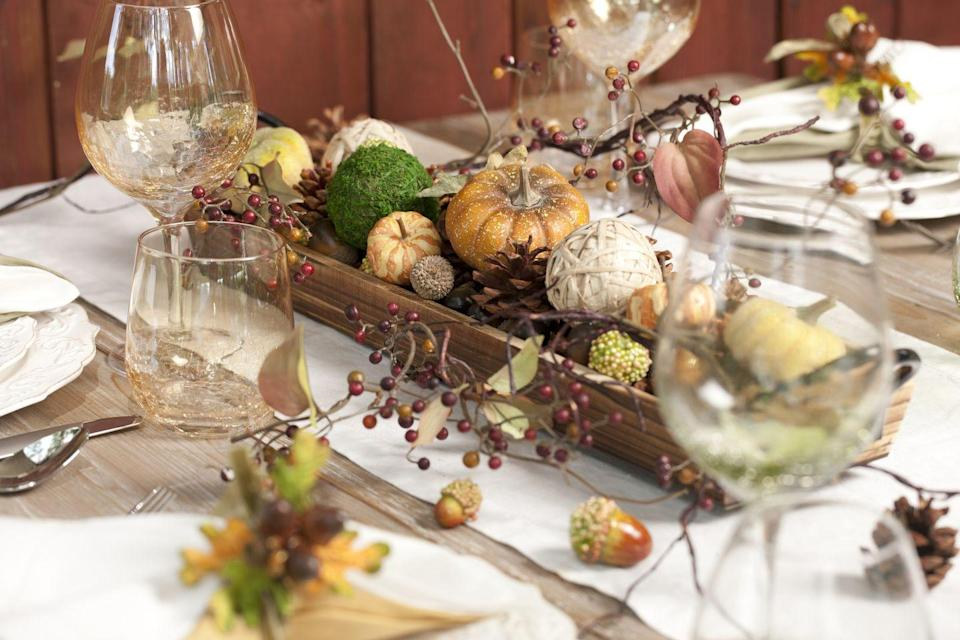 <p>Fill a long wooden tray with a festive medley of gourds, acorns, berry branches, and moss balls.</p>