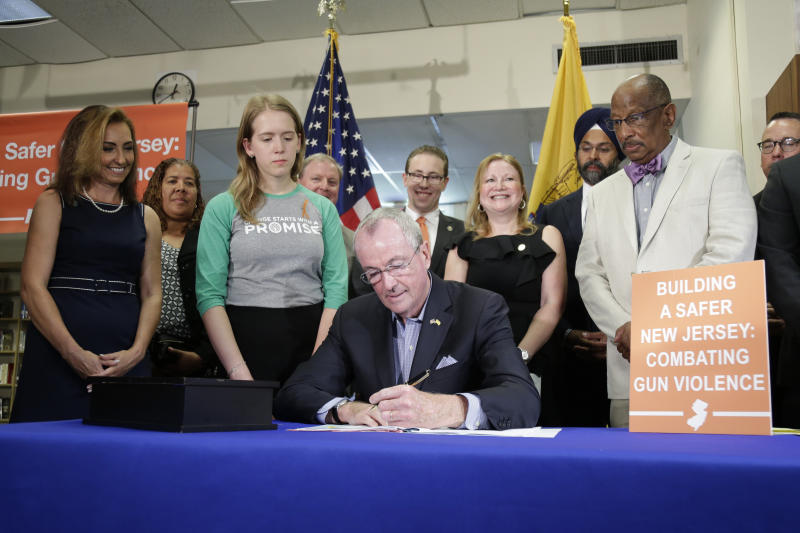 New Jersey Gov. Phil Murphy, center, signs a gun control bill during a ceremony in Berkeley Heights, N.J., Tuesday, July 16, 2019. Murphy has signed a measure aimed at making so-called smart guns available in the state. He also signed three other measures aimed at reining in gun violence. (AP Photo/Seth Wenig)