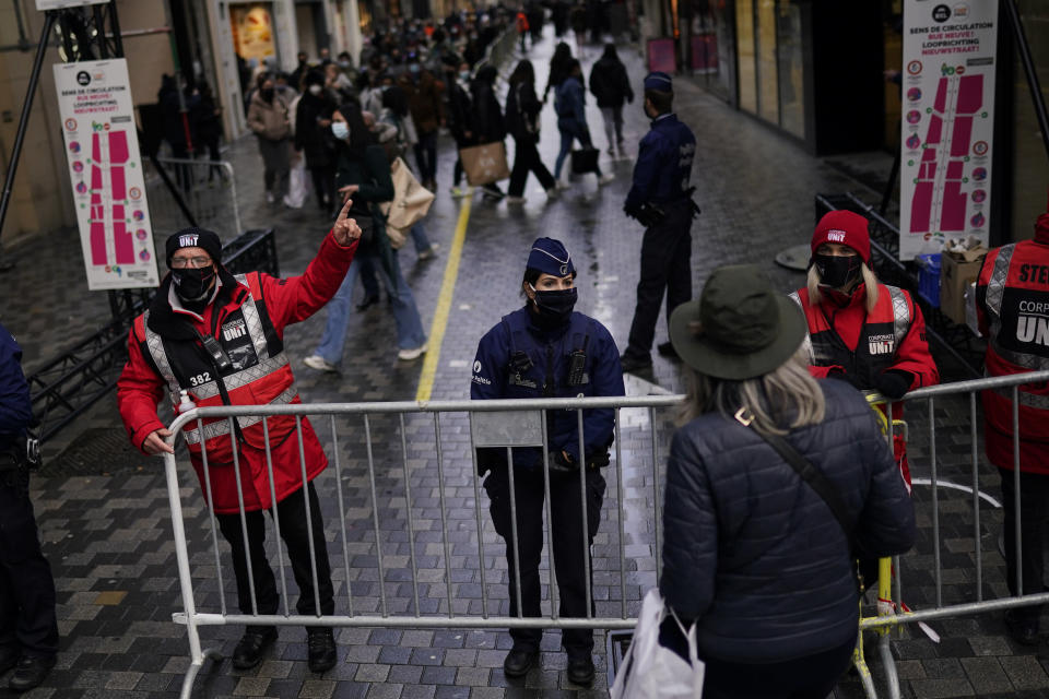 Belgium police officers and security personnel, wearing face mask to prevent the spread of the coronavirus, block temporary an entrance of a commercial street to avoid crowds in downtown Brussels, Tuesday, Dec. 1, 2020. Non-essential shops in Belgium are reopening on Tuesday in the wake of encouraging figures about declining infection rates and hospital admissions because of the coronavirus. (AP Photo/Francisco Seco)