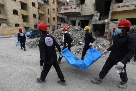 Rescue workers carry a body in Raqqa, Syria April 9, 2018. Picture taken April 9, 2018. REUTERS/Aboud Hamam