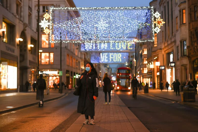 FILE PHOTO: A pedestrian wearing a face mask stands under Christmas lights at Oxford Street amid the coronavirus disease (COVID-19) outbreak in London