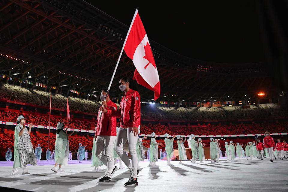<p>TOKYO, JAPAN - JULY 23: Flag bearers Miranda Ayim and Nathan Hirayama of Team Canada lead their team during the Opening Ceremony of the Tokyo 2020 Olympic Games at Olympic Stadium on July 23, 2021 in Tokyo, Japan. (Photo by Matthias Hangst/Getty Images)</p>
