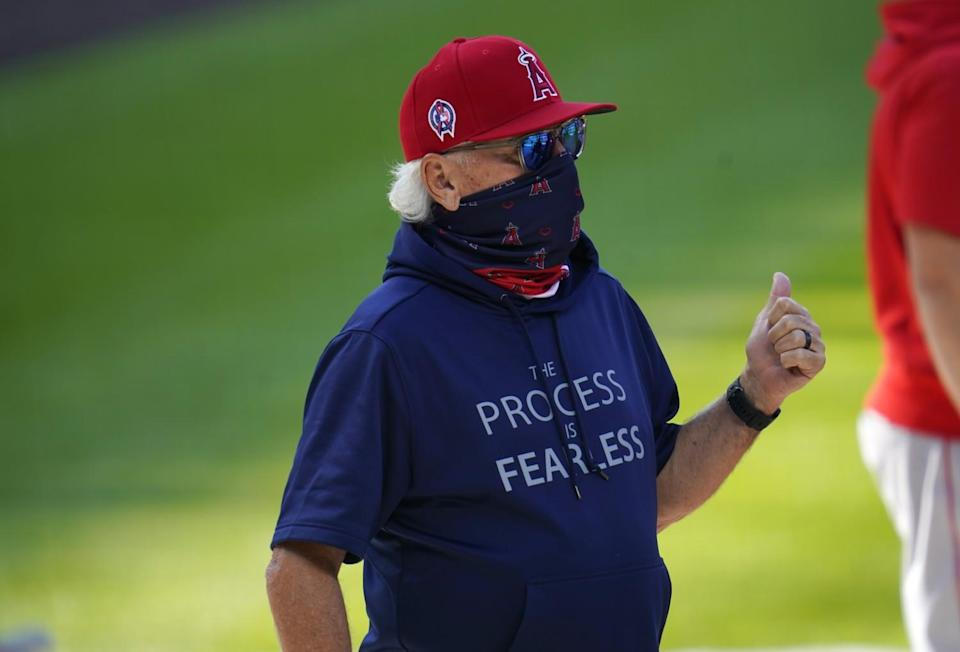 Angels manager Joe Maddon confers with a player as he warms up before a game against Colorado on Sept. 12, 2020, in Denver.