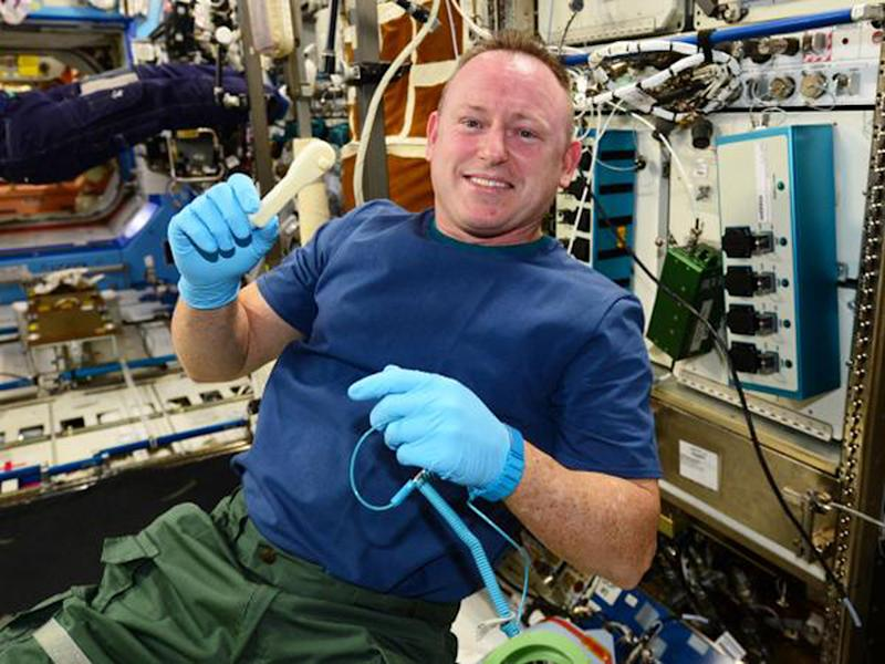 This NASA photo obtained December 20, 2014, shows ISS Commander Butch Wilmore holding up a ratchet after removing it from a print tray