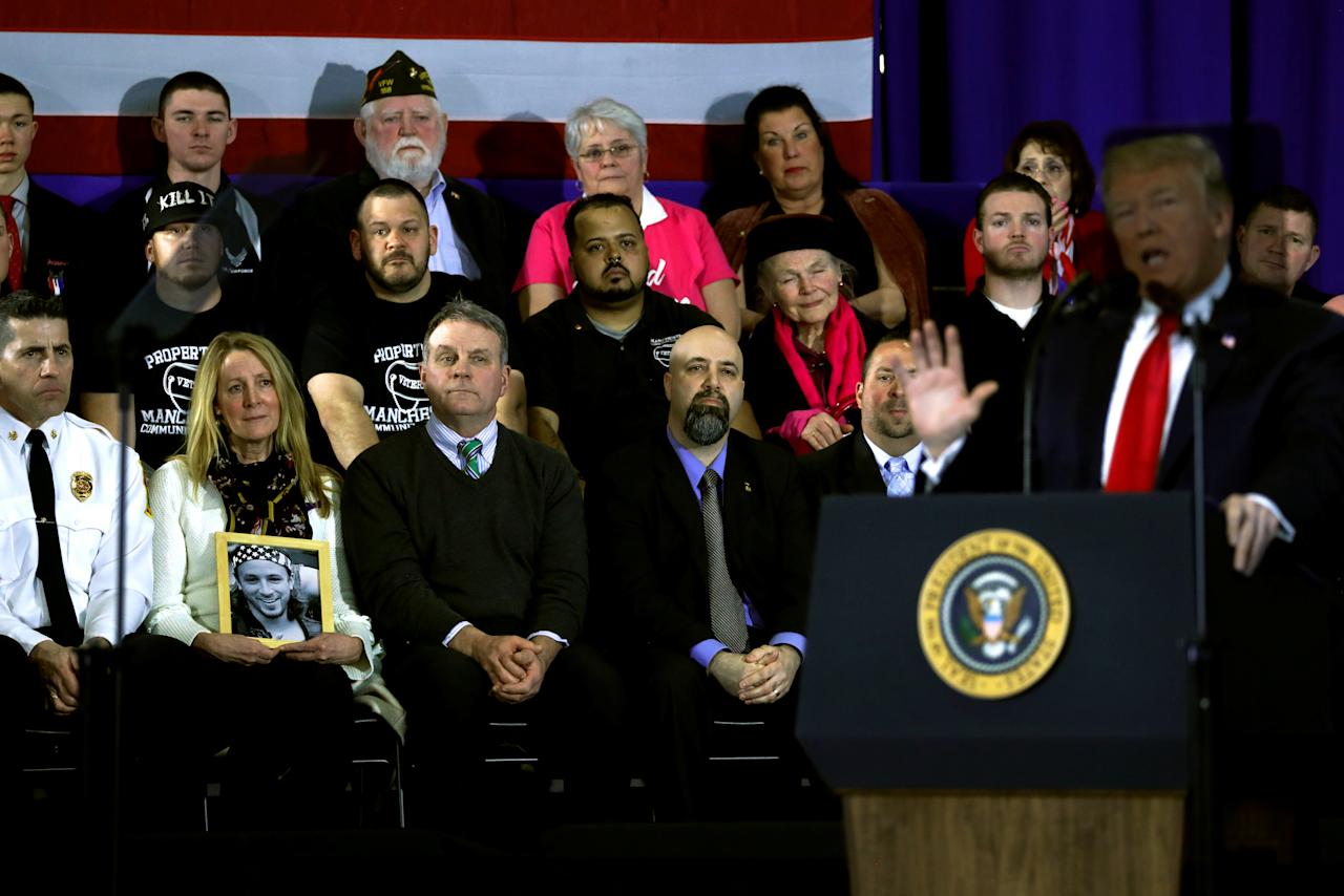 Grieving parents Jeanne and Jim Moser (2nd and 3rd L), holding a picture of their son Adam who died from a drug overdose, sit next to the stage as U.S. President Donald Trump delivers remarks on the U.S. opioid crisis, at Manchester Community College in Manchester, New Hampshire, U.S., March 19, 2018. REUTERS/Jonathan Ernst