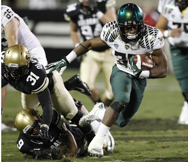 Oregon running back Ayele Forde, right, gets away from Colorado outside linebacker Kenneth Olugbode, top left, and defensive backer Tedric Thompson for a long gain in the fourth quarter of Oregon's 57-16 victory in an NCAA college football game in Boulder, Colo., on Saturday, Oct. 5, 2013. (AP Photo/David Zalubowski)